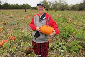 Man, smiling, standing in a pumpkin patch holding a pumpkin