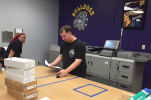 Primary: Man stapling papers together, Secondary: large printer and woman watching, Background: Ark City Bulldogs logo painted on the wall