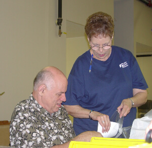 Woman helping man place papers inside plastic bags